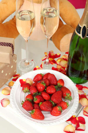 Romantic still life with champagne, strawberry and petals of roses close-up photo