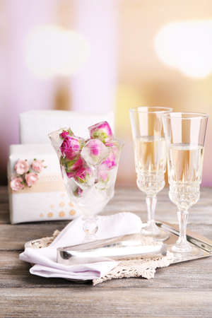 Ice cubes with rose flowers in glass bowl and two glasses with champagne on wooden table, on bright background photo