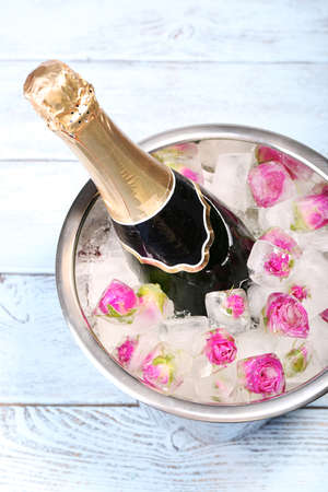 Frozen rose flowers in ice cubes and champagne bottle in bucket, on light background Stock Photo