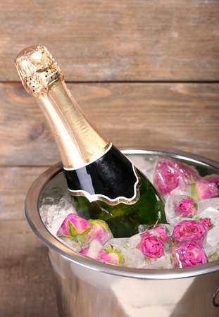 Frozen rose flowers in ice cubes and champagne bottle in bucket, on wooden background photo