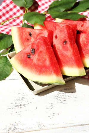 Fresh slices of watermelon on table, outdoors photo