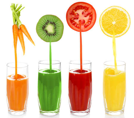 Juice pouring from fruits and vegetables into glass, isolated on white photo