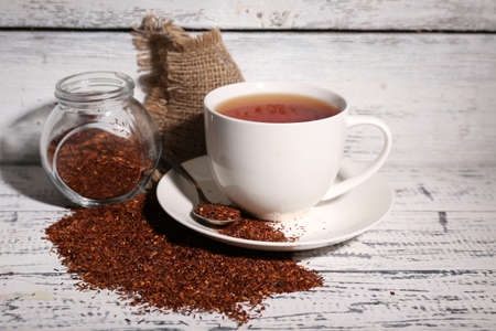 infuser: Cup of tasty rooibos tea, on old white wooden table