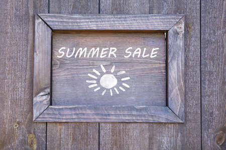 Summer sale written on wooden frame, close-up photo