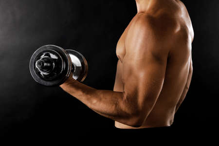 musculation: Athletic man execute exercise with dumbbells, on black background