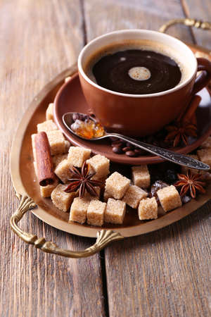 Brown sugar, spices and cup of coffee on tray, on wooden background photo