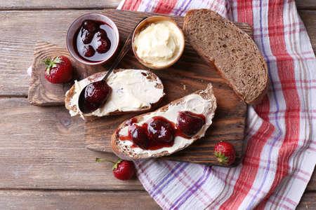 mantequilla: Tostadas con mantequilla y mermelada casera de fresa en el fondo de madera Foto de archivo