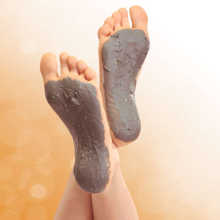 Woman foots with cosmetic clay on bright background photo