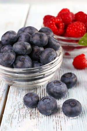 Glass bowls of raspberries and blueberries on wooden background photo
