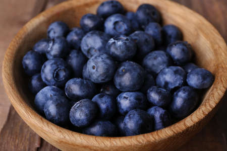 Wooden bowl of blueberries on wooden background closeup