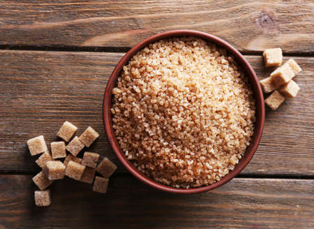 brown sugar: Brown sugar cubes and crystal sugar in bowl on wooden background Stock Photo