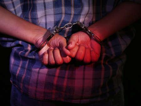 restraints: Criminal hands locked in handcuffs on dark background
