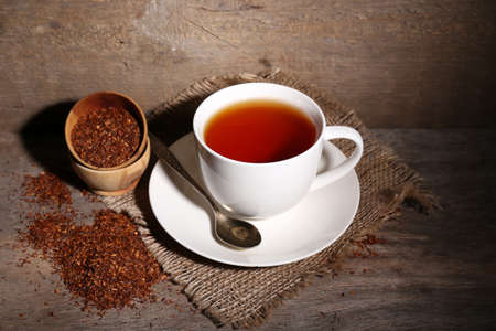 infuser: Cup of tasty rooibos tea, on wooden table