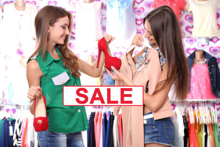 Concept of discount. Two beautiful young woman in shop photo