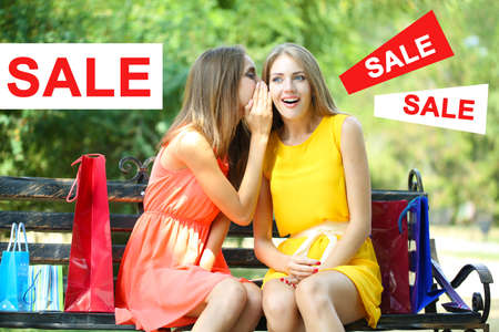 Concept of discount. Two beautiful young woman with shopping bags at park photo