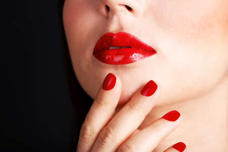 Womans red lips and nails on dark background photo