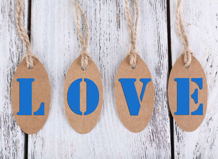Love tags on wooden background photo