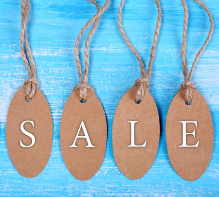 Sale tags on wooden background photo