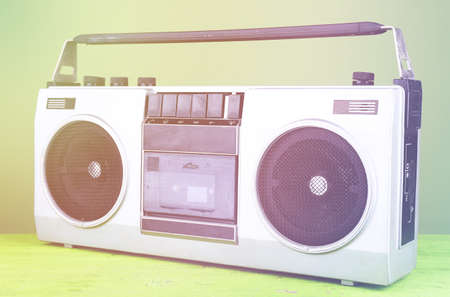 Retro cassette stereo recorder on table on green background photo