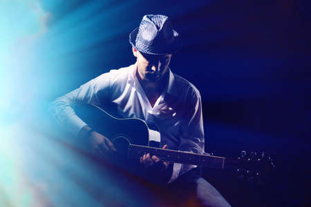 어두운 배경에 어쿠스틱 기타를 연주 젊은 음악가,