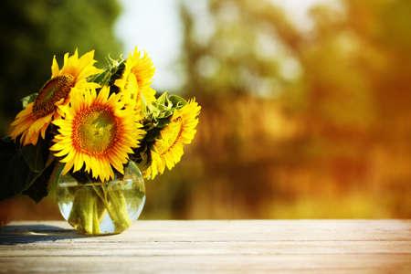 flower vase: Beautiful sunflowers on table on bright background