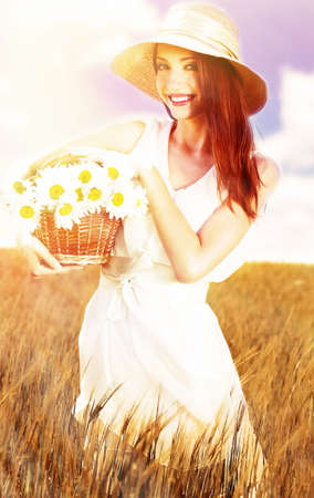 spikelets: Portrait of beautiful young woman with flowers in the field Stock Photo