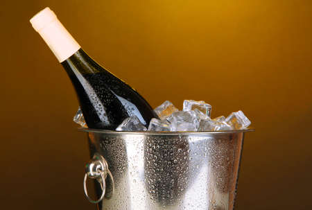 darck: Bottle of wine in ice bucket on darck yellow background Stock Photo