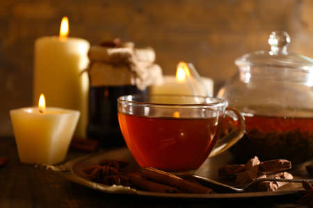 Composition with tea in cup and teapot and candles on table, on wooden background photo