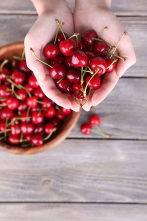 Ripe sweet cherries in hands on wooden background photo