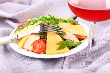 Fresh salad with arugula on fabric background photo