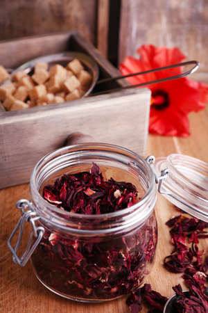 Dried hibiscus tea in glass jar, fresh hibiscus flower and brown sugar in box, on wooden background photo