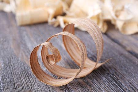 filings: Wood shavings on grey wooden background closeup