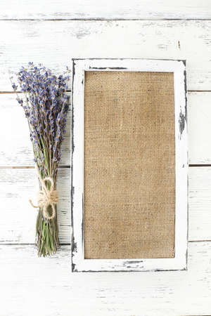 Lavender flowers and wooden frame on wooden background photo