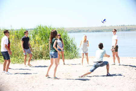 Beautiful young people playing volleyball on beach photo
