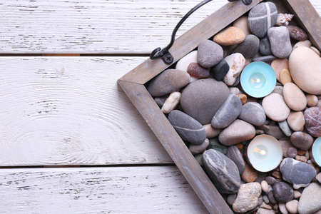 Candles on vintage tray with sea pebbles, on wooden background photo