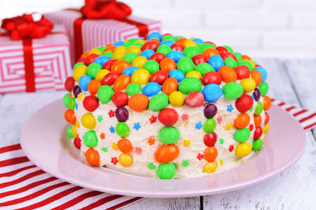 Delicious rainbow cake on plate on table close-up photo