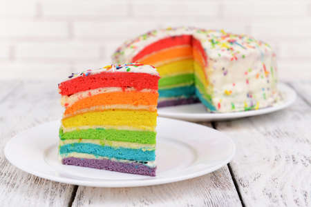 Delicious rainbow cake on plate on table on light background Stok Fotoğraf