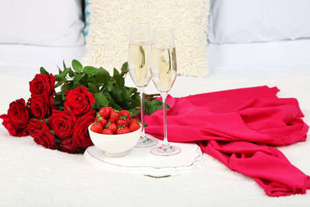Romantic still life with champagne, strawberry and roses on bed photo
