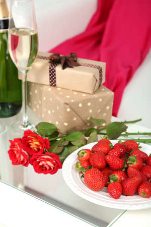 Romantic still life with champagne, strawberry and roses in room photo
