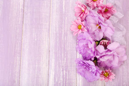 purple flowers: beautiful chrysanthemum and artificial eustoma flowers on purple wooden background