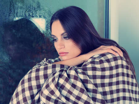 ojos tristes: Mujer sola triste que se sienta en la ventana Foto de archivo