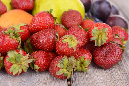 Ripe fruits and strawberries on table close up photo