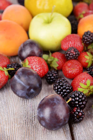 Ripe fruits and berries on wooden background photo