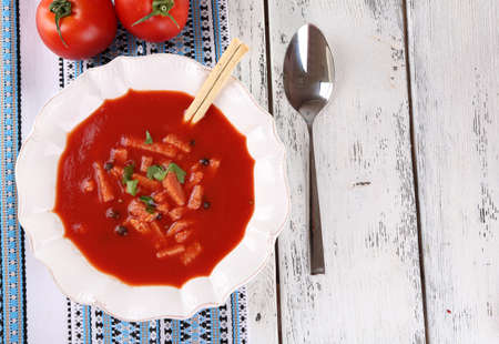 Tasty tomato soup with croutons on table close-up photo