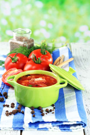 Tasty tomato soup with croutons on table on natural background photo