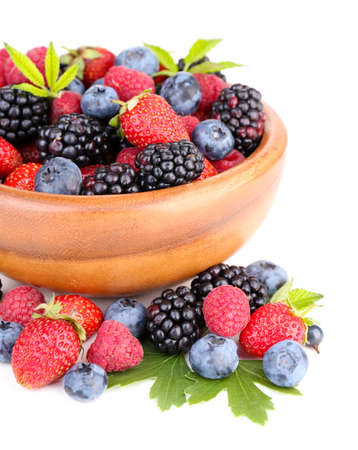 Ripe sweet different berries in wooden bowl, isolated on white photo