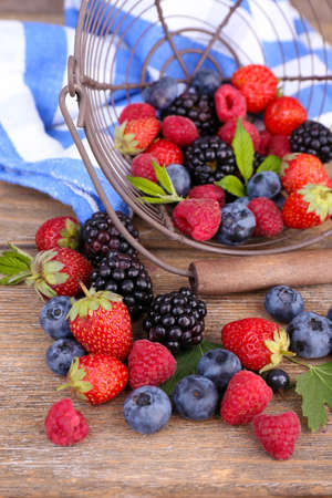 Ripe sweet different berries in metal basket, on old wooden table photo