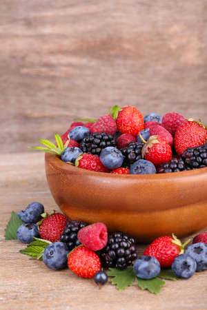 Ripe sweet different berries in bowl, on old wooden table photo