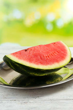 Fresh slice of watermelon on table outdoors, close up photo