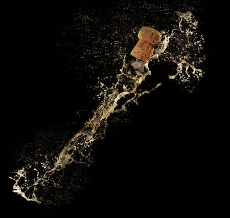 popping cork: Champagne splashes with cork on black background
